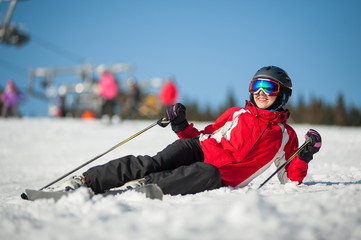 Woman wearing ski goggles, helmet, red jacket, gloves and pants lying with skis on snowy at mountain top and looking away in sunny day with ski lifts and blue sky in background. Carpathian mountains