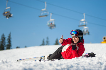 Smiling girl lying with skis on snowy at mountain top, showing thumb up gesture of good class and looking at the camera in sunny day at a winter resort with ski lifts and blue sky in background