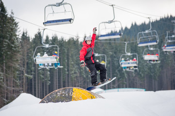 Man on the snowboard jumping over a hurdle in winter day with ski lifts in background at a winter resort