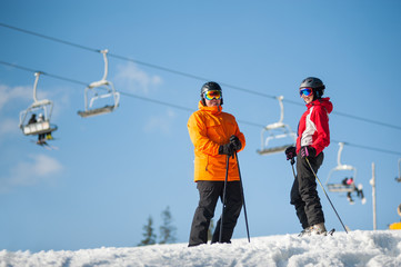 Couple male and female wearing ski goggles standing with skis on mountain top at a winter resort in sunny day with ski lifts and blue sky in background.