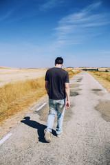 Hombre joven caminando por una carretera vacía