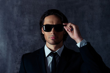 Portrait of serious bodyguard touching his black glasses