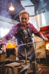 Glassblower forming and shaping a molten glass