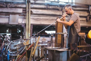 Side view of glassblower shaping glass on blowpipe in factory