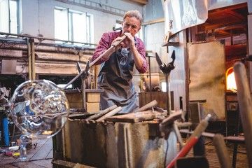 Glassblower working in factory