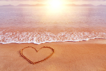Amazing sea sunrise view with a hand drawn heart as love symbol
