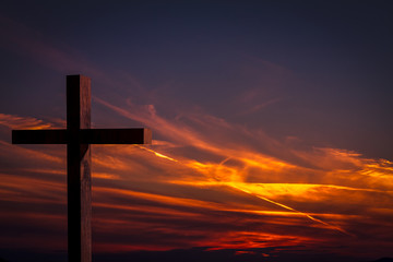 Jesus Christ cross. Christian wooden cross on a background with dramatic lighting, colorful sunset, twilight and orange -  purple clouds and sky.  Easter, resurrection,Good Friday concept