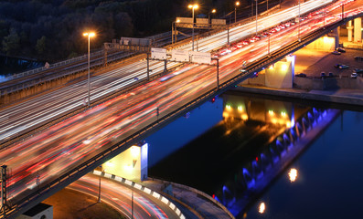 Road bridge across the river at night, view from above. light trails of cars on a highway. Traffic jam on a long exposure