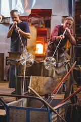 Glassblower shaping glass on blowpipe