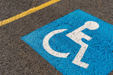 disabled blue parking sign painted on dark asphalt in Canada