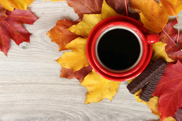 Cup of coffee and cookies on the wooden table with autumn leaves. Autumn breakfast.
