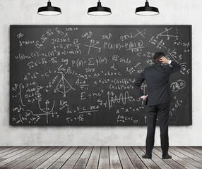 Man in suit looking at blackboard with formulas
