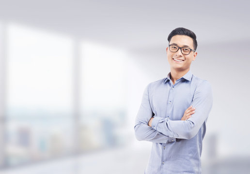 Smiling Asian businessman in blurred office
