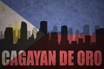 abstract silhouette of the city with text Cagayan de Oro at the vintage philippines flag background