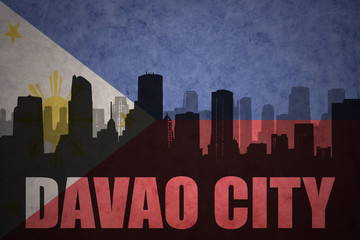 abstract silhouette of the city with text Davao City at the vintage philippines flag background