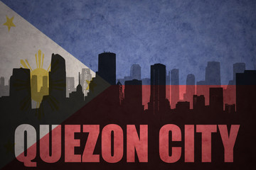 abstract silhouette of the city with text Quezon City at the vintage philippines flag background