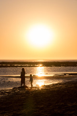 Silhouette of two children at low tide at sunset