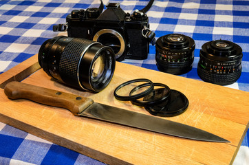 Old vintage camera and lenses on a chopping board, with filters positioned like cooking ingredients sliced with a knife