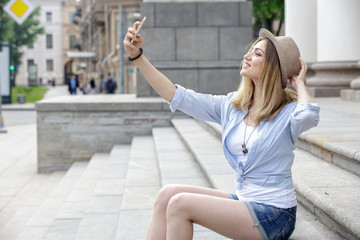 Beautiful woman tourist making selfie on the steps of the historic building. Girl blonde, wearing a white T-shirt, blue shirt and blue denim shorts, a hat on her head. Summer. Outdoors.