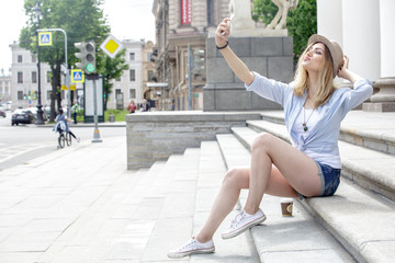 Beautiful woman tourist making selfie on the steps of the historic building. Girl blonde, wearing a white T-shirt, blue shirt and blue denim shorts, a hat on her head. Summer. Outdoors. Duck face.