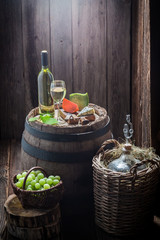 Homemade chardonnay wine in glass with cheese and grapes