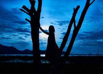 silhouette picture of woman stands on the dead tree in the night. Halloween and witch concept. There is the moon in the night sky.