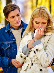 Girl is crying and telling guy about an unwanted pregnancy. Man tries to persuade her not to have an abortion. Girl is crying with handkerchief on fall park outdoor.