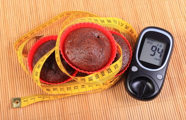 Glucometer, muffins in red cups and tape measure