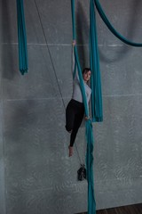 Gymnast exercising on blue fabric rope
