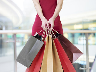 young woman carrying shopping bags standing in mall, focus on the hands