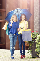 Young and happy women with shopping bags in the city