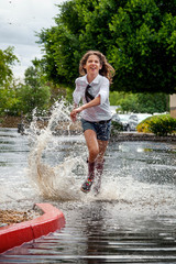 Enthusiastic Girl Runs Through a Puddle in a Parking Lot