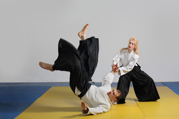 martial art of Aikido.  girl and  man demonstrate  techniques of