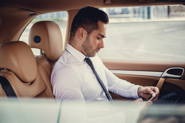Stylish male in a white shirt using smartphone.