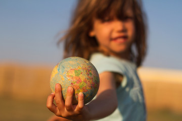 Child hand holding an earth toy globe