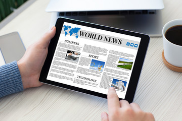 male hands holding tablet computer world news table notebook pho