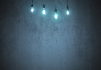 tungsten light bulb on empty blue wall with copy space for inspiration or idea under light bulb