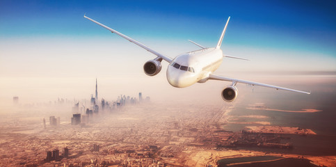 Commercial airplane flying over modern city Wall mural