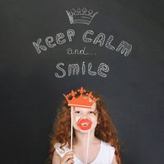 Funny girl with carnival crown and lips showing her teeth, stand