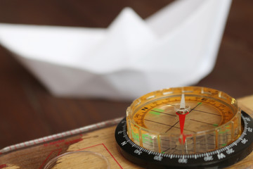 Columbus Day. A compass and a paper boat in a blur for the background.10 st October in the United States celebrated Columbus Day.