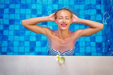Enjoying vacation. Smiling beautiful young woman in swimming pool.