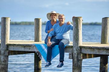 älteres Paar sitzt gemeinsam am See, genießen den Tag