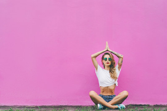 Colorful yoga. Attractive young woman sitting on lotus position on the ground against pink wall.