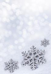 Glass toy snowflake on snow background.