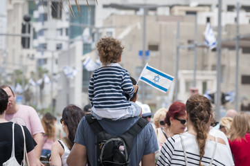 Father and a child walking with the crowd in the Tel Aviv promenade during the Independence Day of Israel. Tel Aviv, Israel, May 2014. Stock photo image.