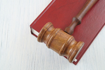 Wooden judge's gavel on red legal book