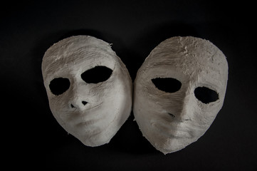 weiße Masken auf schwarzem Hintergrund