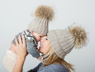 Mother and baby in knitted cap playing and smiling. Happy family