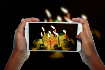 photographing birthday cupcake with candle by phone