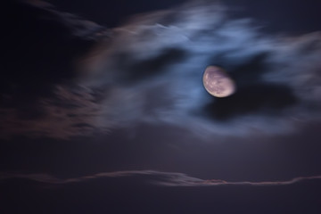 The moon behind clouds in the night sky.